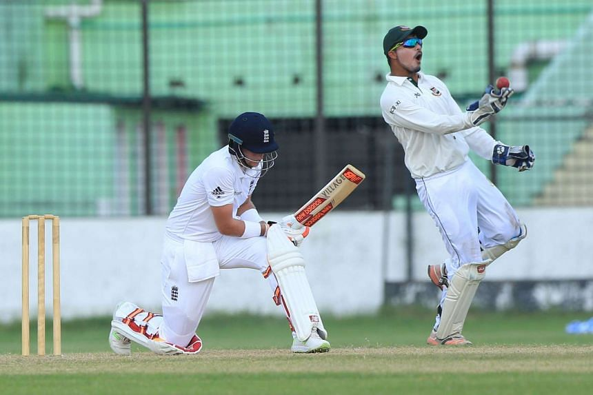 England cricketer Joe Root is caught by Nurul Hasan (right) during the warm-up match between England and the Bangladesh Cricket Board XI at the MA Aziz Stadium in Chittagong on Oct 17, 2016.
