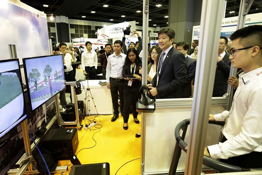 Assistant Professor Xu Hong (on minister's right) showing Senior Minister of State for Transport Ng Chee Meng the walking simulator at the Singapore International Transport Congress and Exhibition 2016 on Oct 19, 2016.
