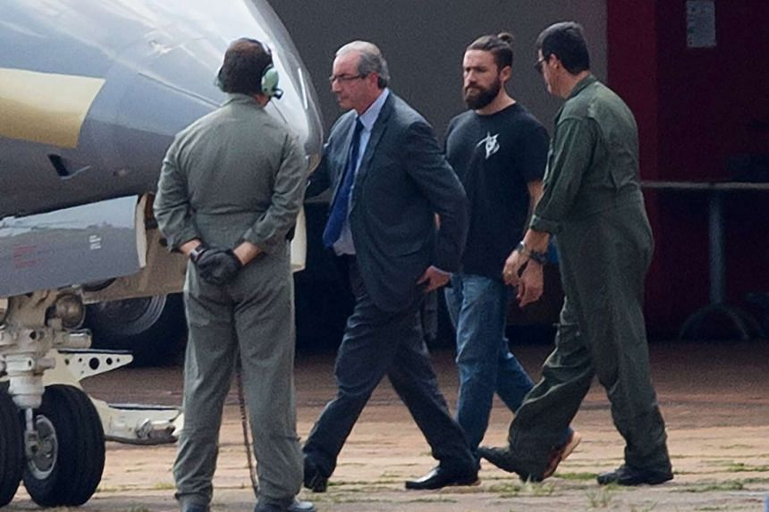 The former president of the Brazilian Chamber of Deputies, Mr Eduardo Cunha (second from left), being escorted to a police plane which took him to Curitiba.