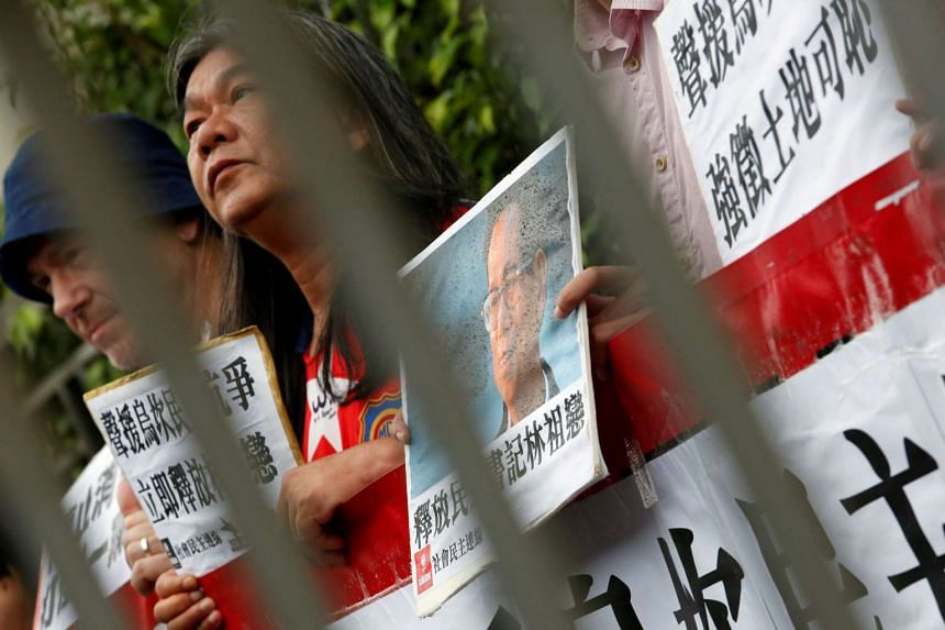 Protesters against the jailing of Lin Zuluan, former head of Wukan village, demonstrate with Lin's portrait outside the China Liaison Office in Hong Kong on Sept 9, 2016.
