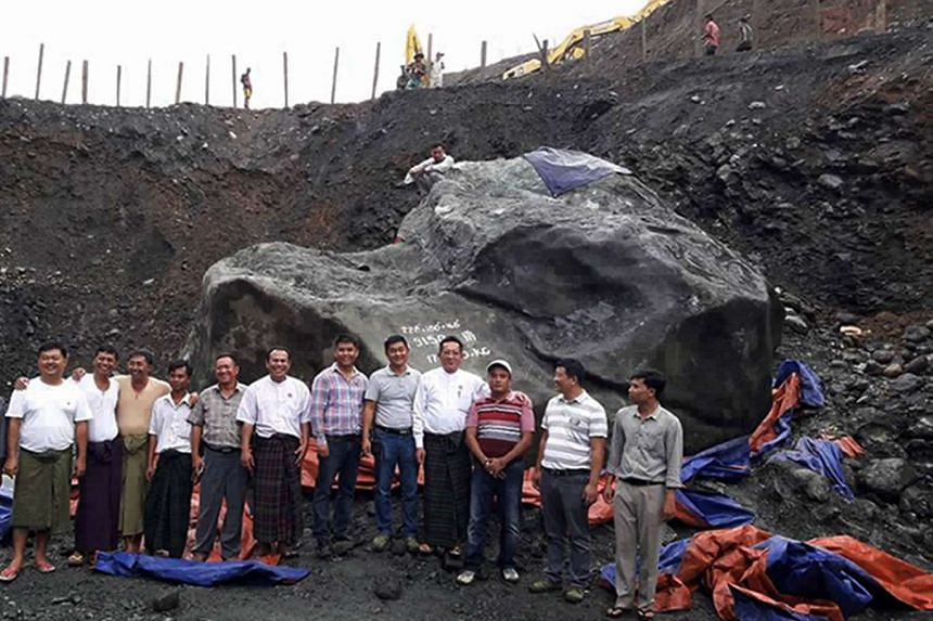 Myanmar Member of Parliament Tint Soe (fourth from right) poses with a group of officials and miners next to the giant jade stone on Oct 13, 2016.