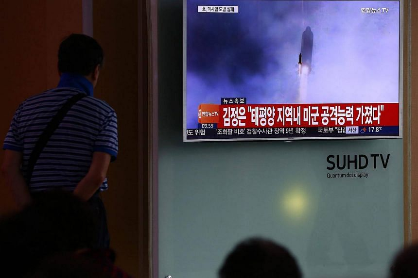 South Koreans watch a television news broadcast at a station in Seoul, South Korea.