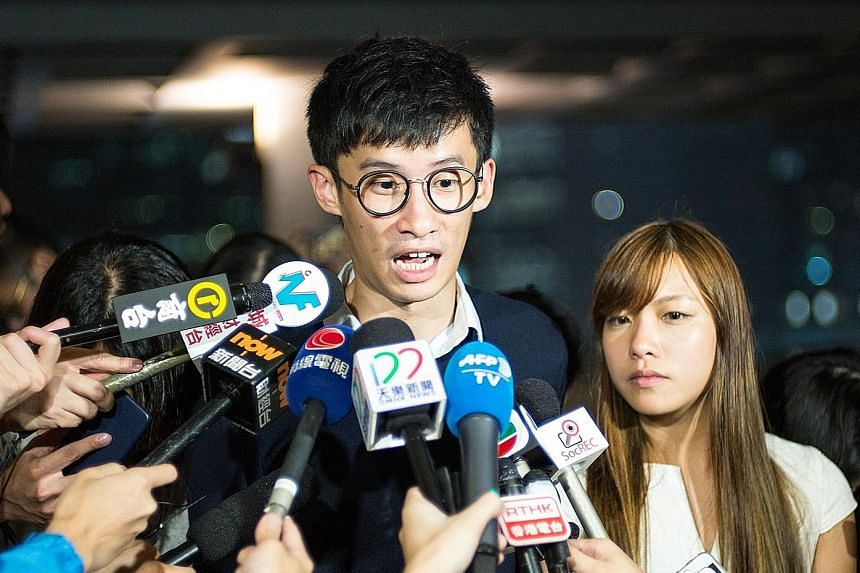 Pro-Beijing lawmakers walking out of the Hong Kong legislature yesterday in protest against the swearing-in of pro-independence lawmakers Baggio Leung and Yau Wai Ching (both below, speaking to the press on Tuesday).