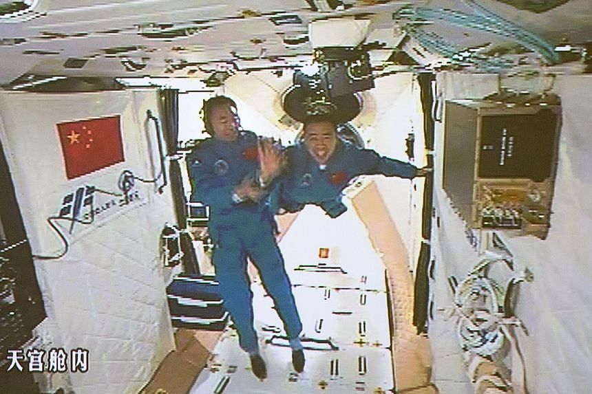Chinese astronauts Jing Haipeng (left) and Chen Dong seen arriving at the Tiangong-2 space station yesterday in a live feed that was telecast on state television. This is Mr Jing's third space mission and Mr Chen's first. They will remain at the spac