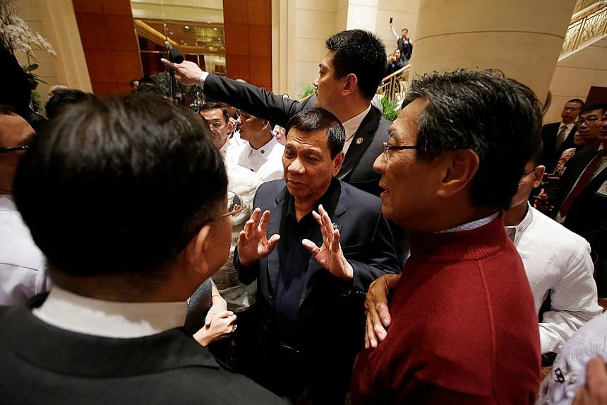 """Mr Duterte (centre) chatting with members of the Filipino community at the Grand Hyatt Beijing hotel in China yesterday. He said that he would be asking for """"the help of China"""" during his four-day state visit."""