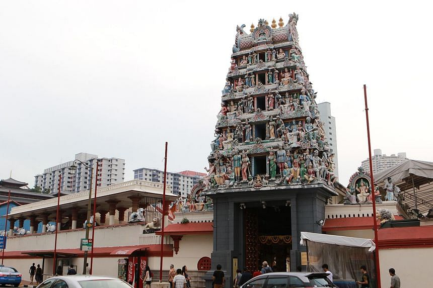 A devotee prays in front of the temple's main prayer hall. Many of the early devotees were Hindus from South India who came to Singapore to work as coolies, craftsmen or merchants. Top: The Sri Mariamman Temple, an enduring icon in Chinatown, has bee