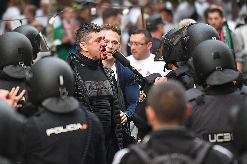 Left: Real Madrid's Gareth Bale celebrating his first European goal in almost two years. His side completed a 5-1 victory in the Champions League group-stage match against Legia Warsaw on Tuesday. Below: Spanish police facing off against supporters o