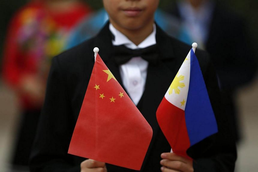 A Chinese boy holds the Chinese and Philippines national flags during a rehearsal for the welcome ceremony for Philippines President Rodrigo Duterte.