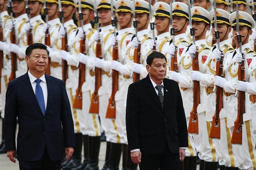 Philippines President Rodrigo Duterte and Chinese President Xi Jinping review honor guards during a welcome ceremony.