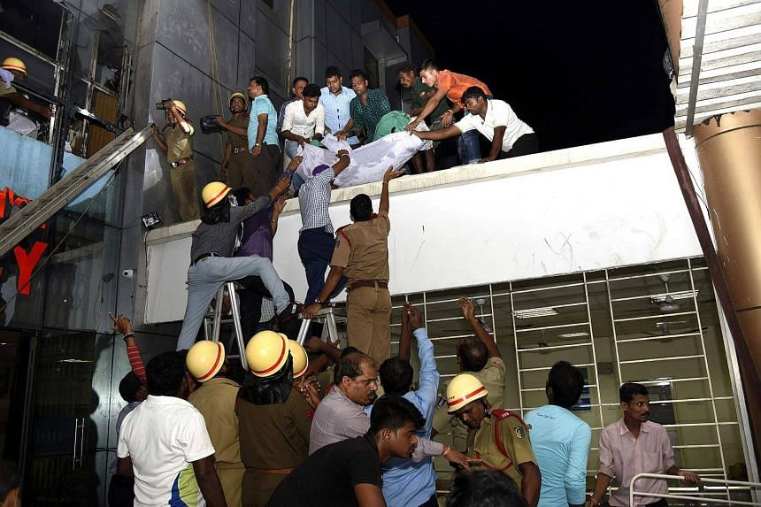 Indian rescue workers lowering a body of a victim of a massive fire at the SUM hospital building in Bhubaneswar.