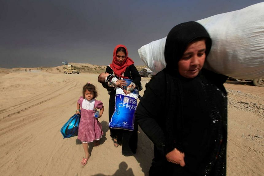 Displaced people fleeing clashes arrive in Qayyarah, during an operation to attack ISIS militants in Mosul, Iraq, Oct 19, 2016.