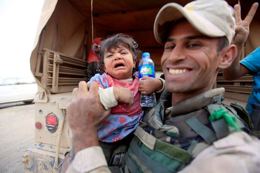 An Iraqi army soldier carries a displaced child fleeing clashes during an operation to attack ISIS militants in Mosul, Iraq, Oct 19, 2016.