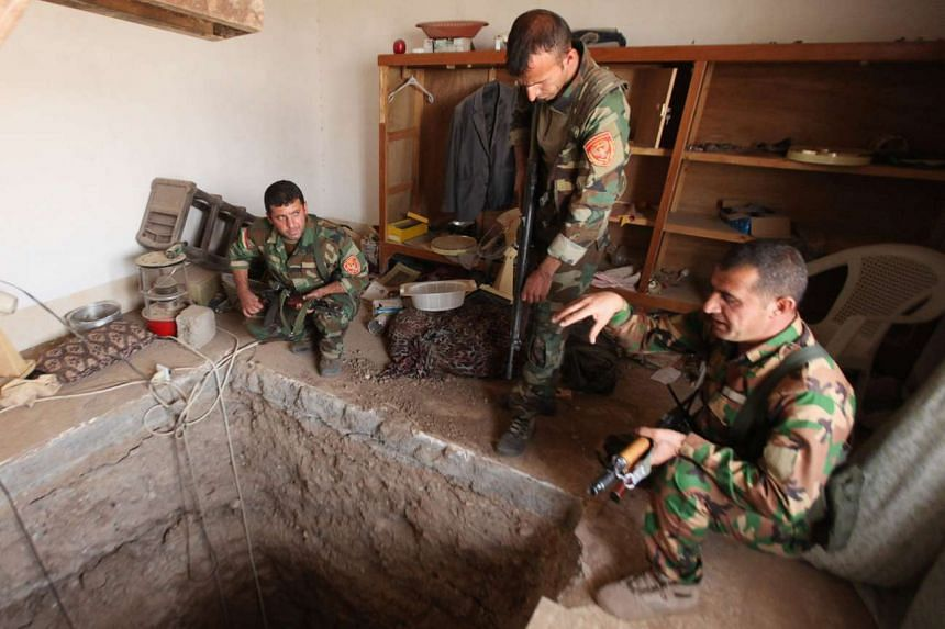Peshmerga forces stand around a tunnel used by ISIS militants in Bartila, east of Mosul, Oct 19, 2016.