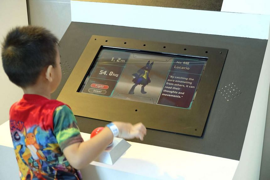 A kid putting his Pokemon on the Answer Station to see if he has got its guess right in the Pokemon Research Exhibition at S.E.A Aquarium in Resorts World Sentosa.