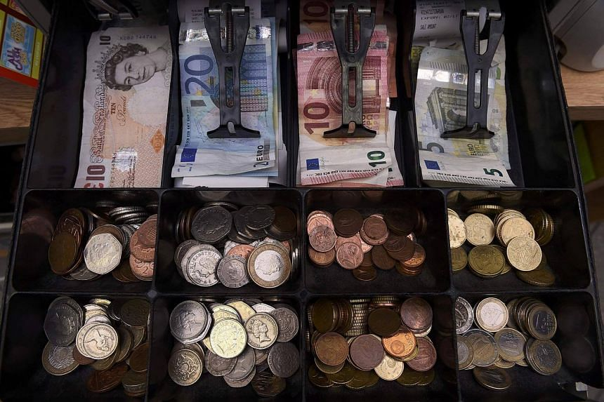 A shop cash register is seen with both Sterling and Euro currency in the till.