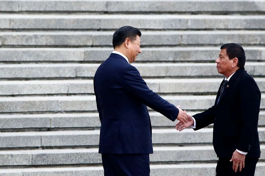 Philippine President Rodrigo Duterte (right) and Chinese President Xi Jinping shake hands as they attend a welcoming ceremony at the Great Hall of the People in Beijing on Oct 20, 2016.