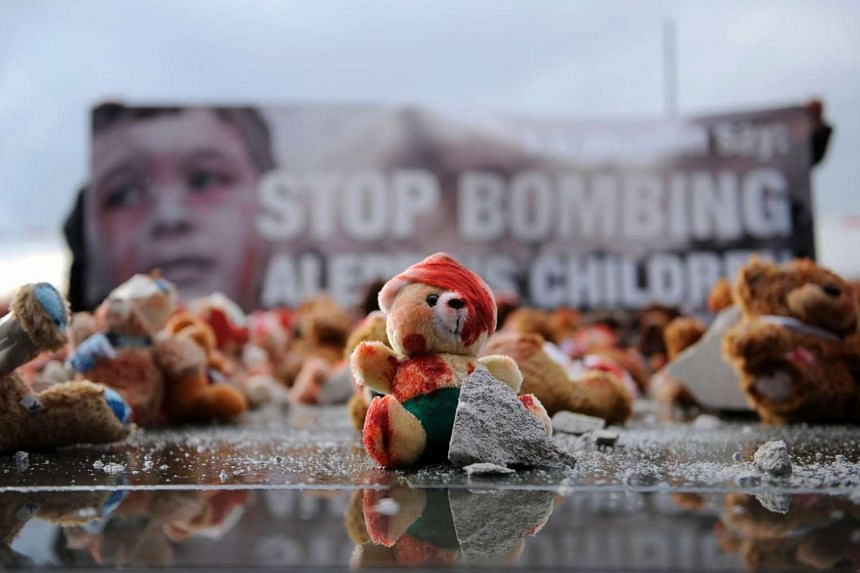 Colour-smeared teddy bears are laid by campaigning group Avaaz to protest against the bombing of Syrian city Aleppo on Oct 19, 2016 in Berlin ahead of a meeting of leaders of Russia, Ukraine, France and Germany.