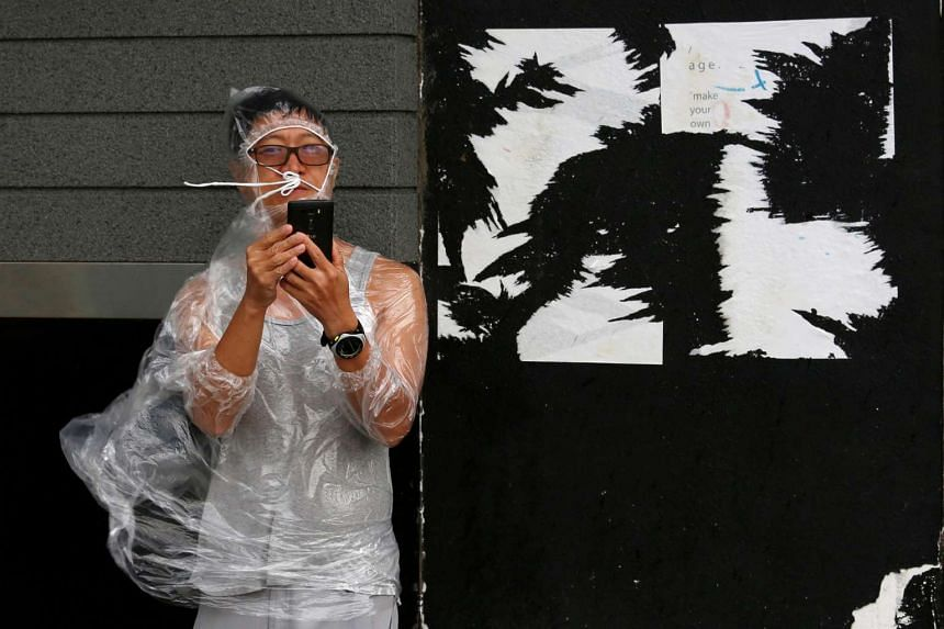 A man uses a smartphone under strong winds near a waterfront as Typhoon Haima approaches in Hong Kong on Oct 21, 2016.