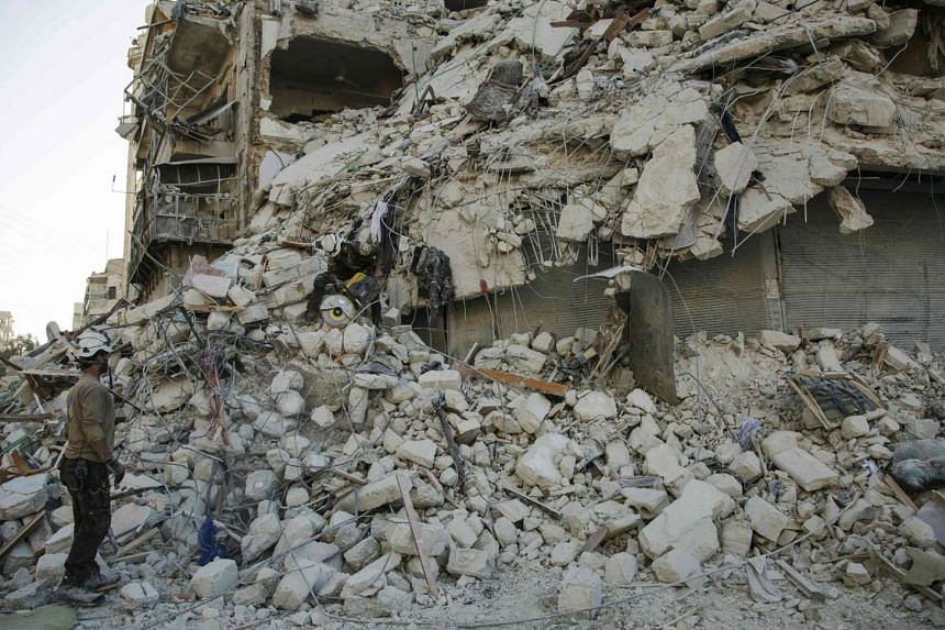 A member of the Syrian Civil Defence stands amid the rubble of a destroyed building during a rescue operation following reported air strikes in the rebel-held Qatarji neighbourhood of Aleppo, on Oct 17, 2016.