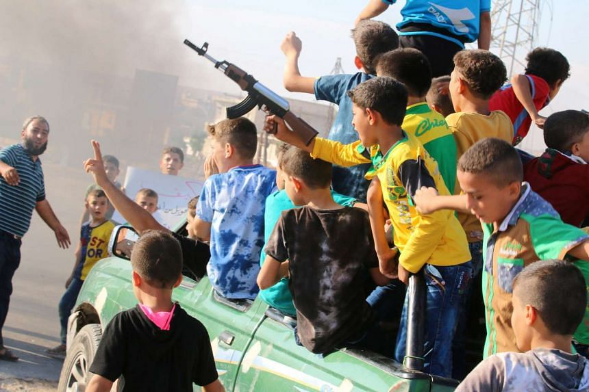 A boy carries a toy gun while riding a pick-up truck during a demonstration calling for aid to reach Aleppo on Sept 14, 2016.
