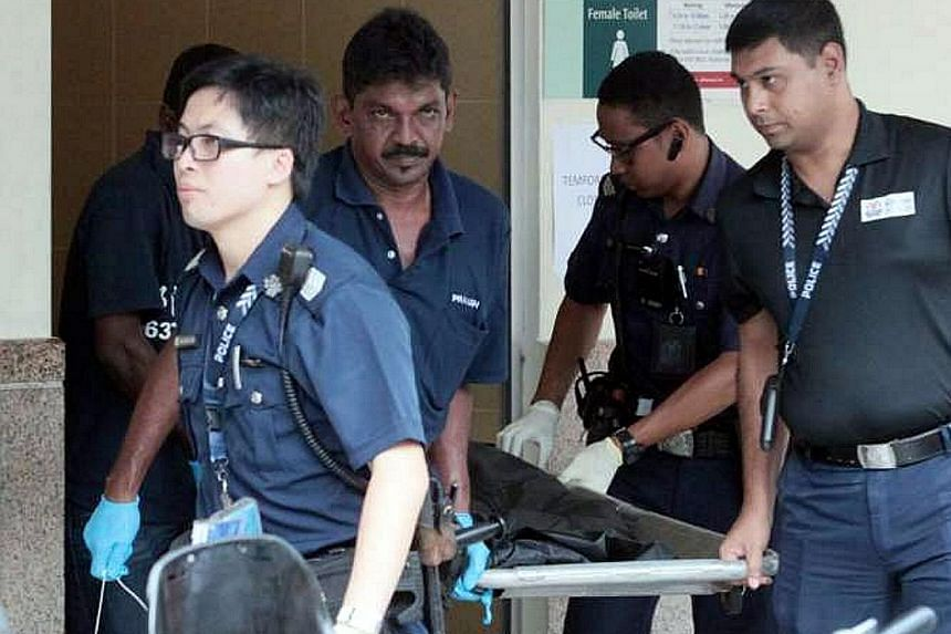 Police officers seen carrying a body bag from a toilet at Tampines MRT station on June 3, where the body of a newborn baby boy was found. An open verdict was recorded at an inquest into the infant's death.