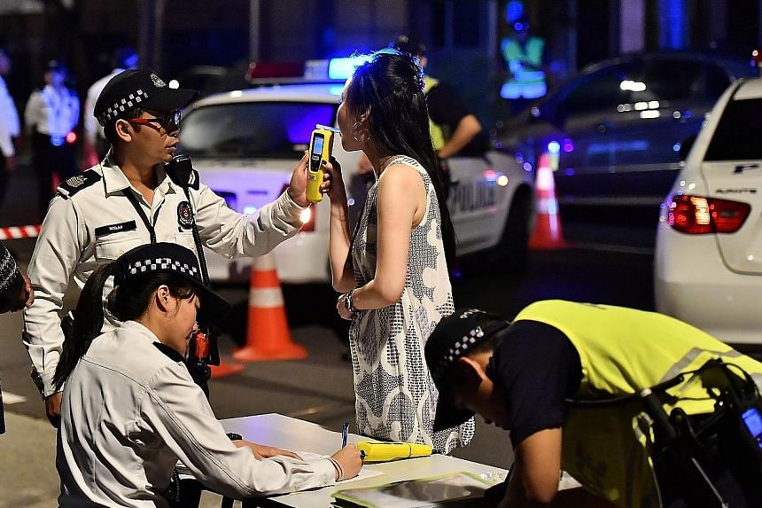 A drink-driving suspect inside a police van. Fifteen men and three women aged between 22 and 58 were arrested in the operation early yesterday morning. A motorist suspected of drink-driving being tested using a hand-held breath analyser. Police held