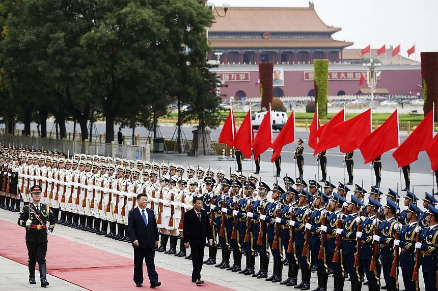 """Mr Xi and Mr Duterte reviewing the honour guard during a welcome ceremony for the Philippine President in Beijing yesterday. Mr Duterte highlighted warm ties, calling China """"a friend of the Philippines""""."""