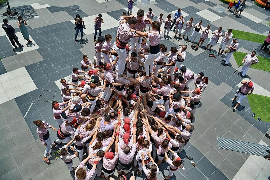Castellers from Spain forming a human tower, or castell, in Sentosa yesterday. The 290 castellers from the Minyons de Terrassa, here as part of Catalan Week, climbed deftly on each other's shoulders, reaching a height of 12.5m. The Catalan tradition,