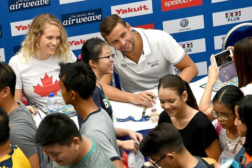 Canadian Olympic bronze medallist Hilary Caldwell and South African ex-Olympic champion Chad le Clos posing for photos during a meet and greet session ahead of the Singapore leg of the Fina/airweave Swimming World Cup.