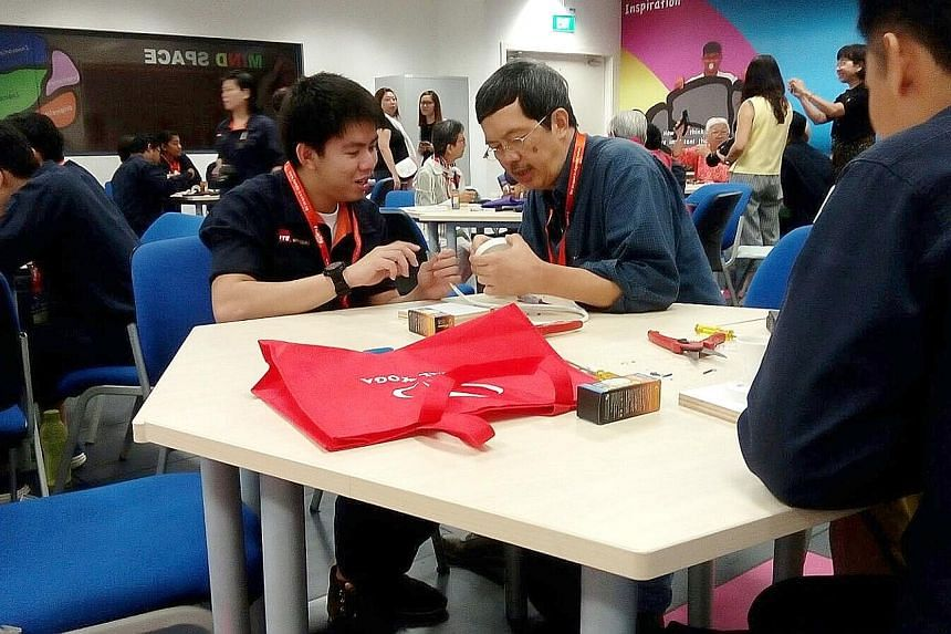 ITE student Marcus Leo and retiree Tom Toh building a table lamp at an Intergenerational Learning Programme course.