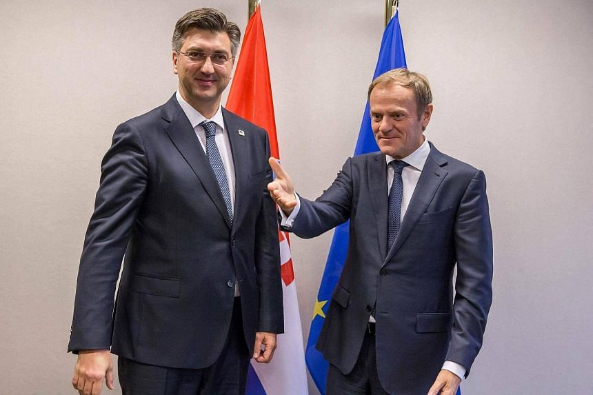 European Union council President Donald Tusk (right) gestures as he welcomes Croatian Prime Minister Andrej Plenkovic (left) ahead of an European Union leaders summit on Oct 20, 2016.