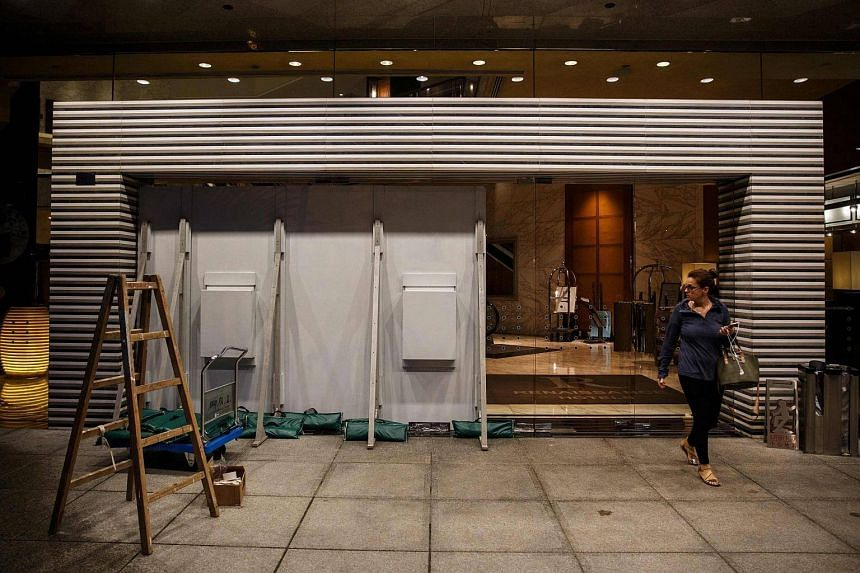 A woman walks past protective wooden boards placed in front of glass doors, as Typhoon Haima approaches Hong Kong early on Oct 21, 2016.