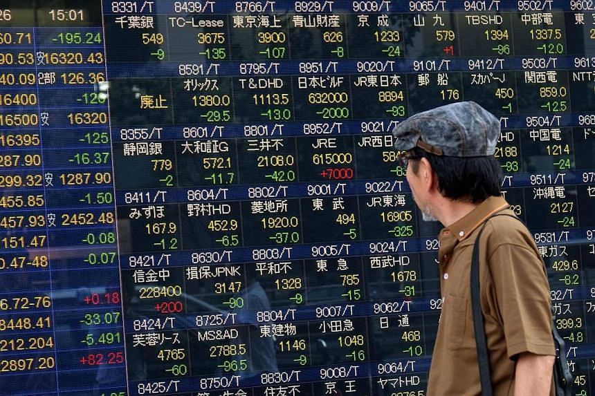A man looks at an electric quotation board displaying the Nikkei key index of the Tokyo Stock Exchange in Tokyo.