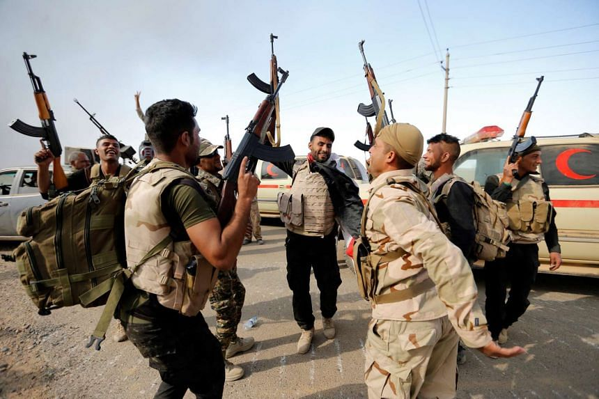 Members of the Iraqi security forces celebrate after the liberation of Khalidiya village from ISIS militants, south of Mosul, Oct 20, 2016.
