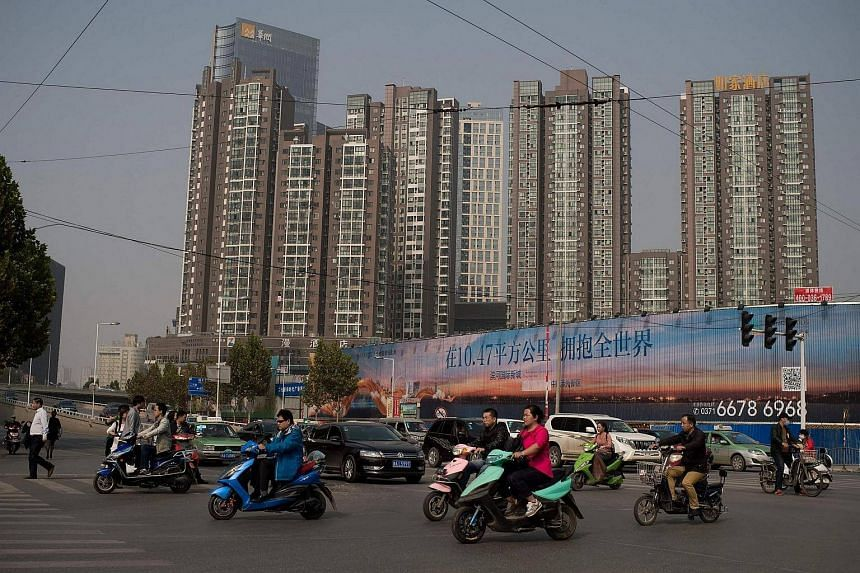 People ride electric bikes as they pass next to property condominiums (back) in Zhengzhou.