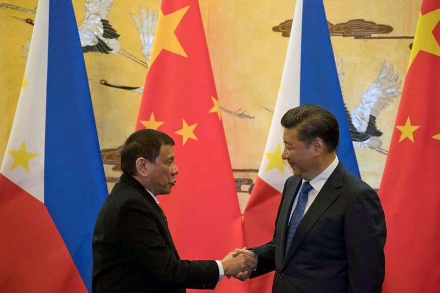 Philippine President Rodrigo Duterte (left) and Chinese President Xi Jinping shake hands in Beijing, Oct 20, 2016.