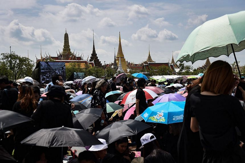 Thousands of mourners clad in black gather in front of the Grand Palace to pay respects to the late Thai King Bhumibol Adulyadej in Bangkok on Oct 22, 2016.