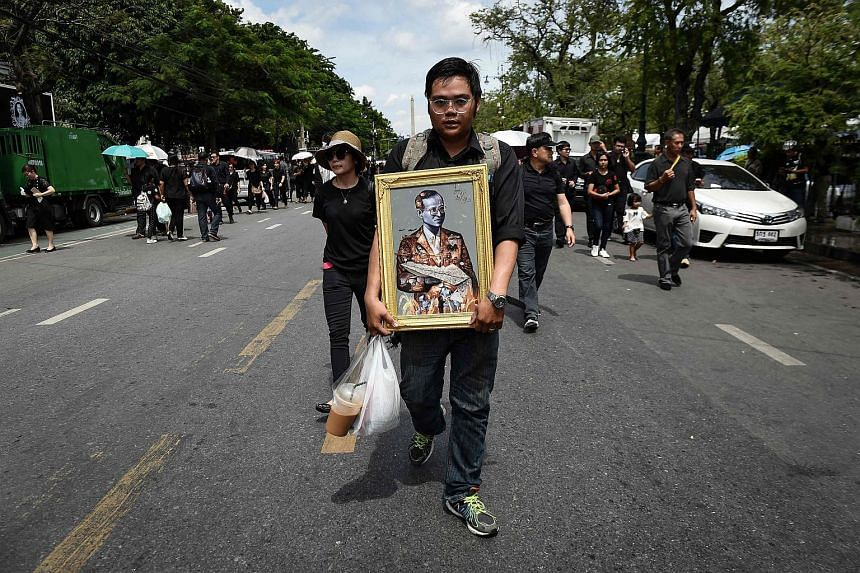 A mourner clad in black carries a painting of the late Thai King Bhumibol Adulyadej to the Grand Palace in Bangkok on Oct 22, 2016.