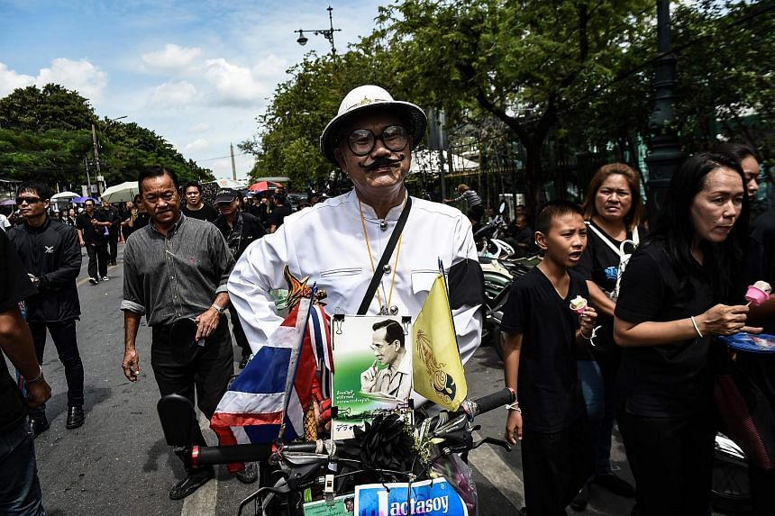 A mourner in a traditional Thai costume displays a picture of Thai King Bhumibol Adulyadej on the front of his motorbike near the Grand Palace in Bangkok on Oct 22, 2016.