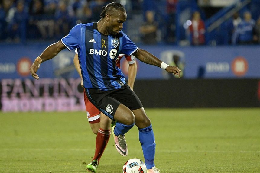 Montreal Impact forward Didier Drogba (11) dribbles the ball during the second half against the New England Revolution at Stade Saputo.