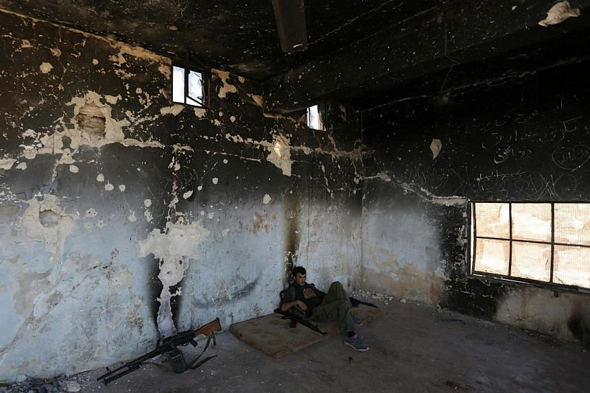 A rebel fighter rests inside a damaged room in Marea city, northern Aleppo province on Oct 21, 2016.