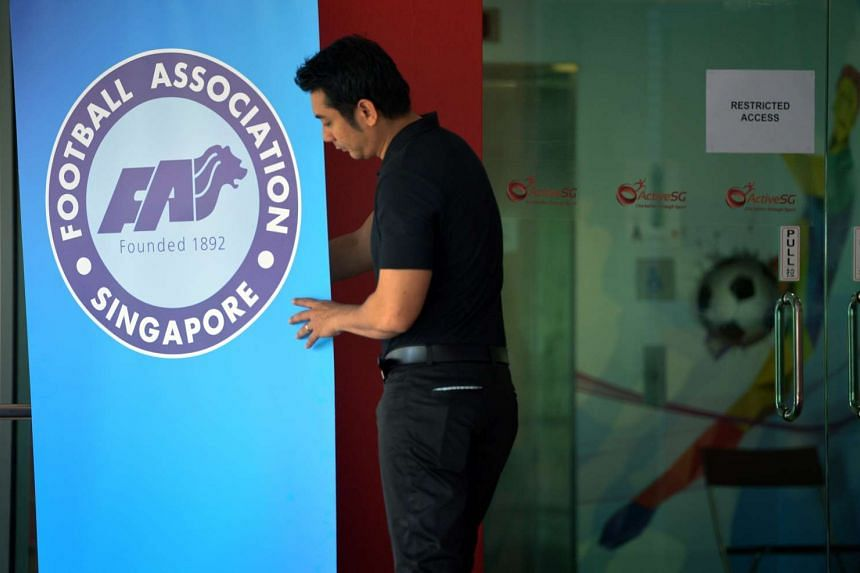 A security personel holding up the Football Association of Singapore (FAS) poster at the Jalan Besar Stadium.