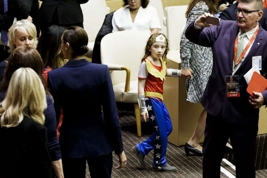 A young girl in a costume looks on as actresses Gal Gadot (4-L), and Lynda Carter (2-L), who have both portrayed the character of Wonder Woman, pose for pictures during an event where the Wonder Woman character was designated as an Honorary Ambassado
