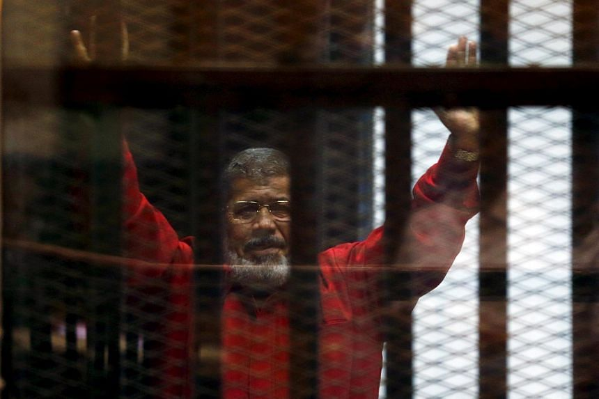 Egypt's deposed president Mohamed Mursi behind bars at a court on the outskirts of Cairo on June 21, 2015. He was sentenced to 20 years in prison on Saturday (Oct 22).