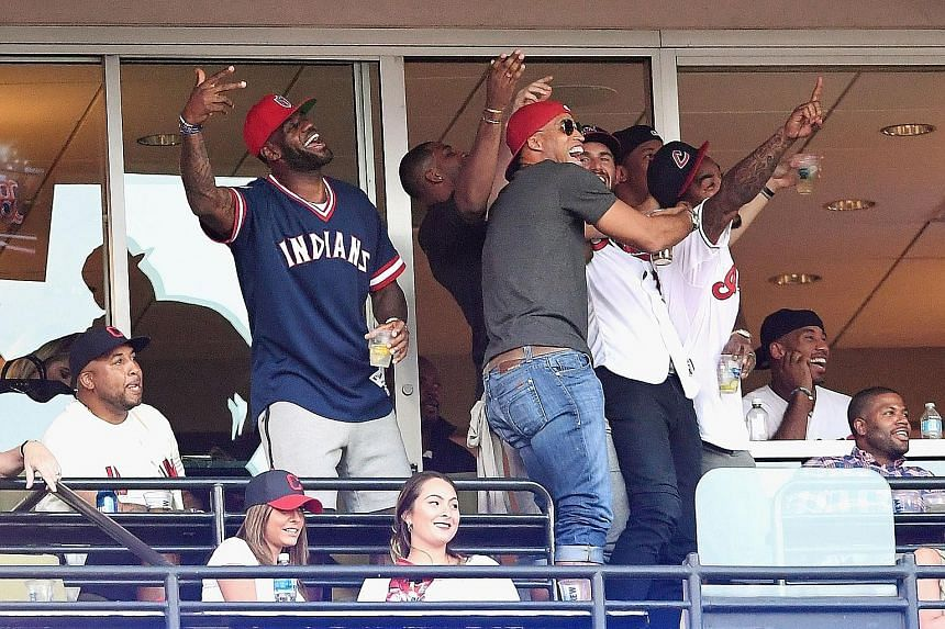 LeBron James (left) and his Cleveland Cavaliers team-mates catching Game 2 of Major League Baseball's American League Division Series between the Boston Red Sox and the Cleveland Indians during the NBA off-season. Earlier this year, the Cavs won Clev