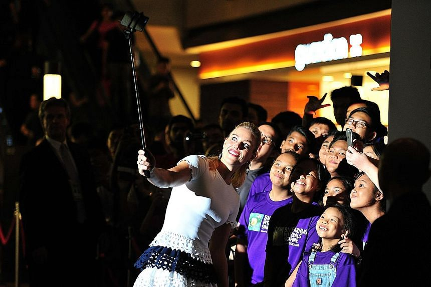 World No. 1 Angelique Kerber taking a selfie with SportCares ambassadors at the WTA Finals singles draw ceremony at Marina Bay Sands.
