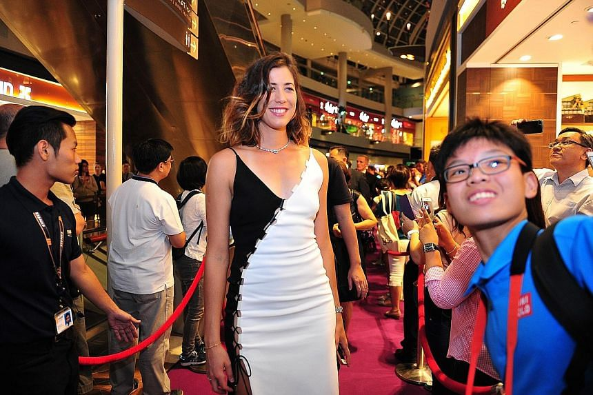 Above: World No. 6 Garbine Muguruza on the purple carpet at the singles draw ceremony at The Shoppes at Marina Bay Sands yesterday. Left: A happy Anjelica Barracoso, who is a fan of Spanish player Muguruza, taking a selfie with her prized pair of WTA