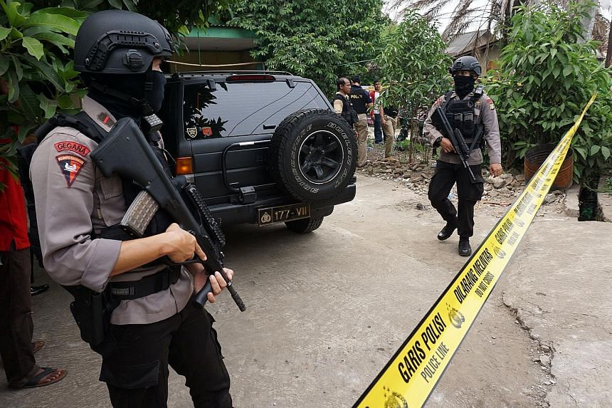 Indonesian anti-terrorist forces outside the home of a suspected ISIS supporter in Banten province on Thursday.