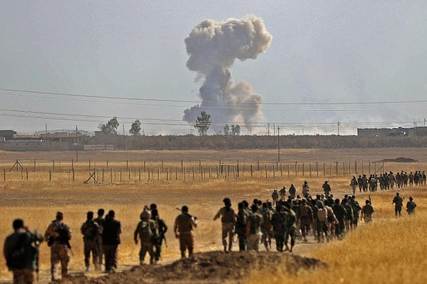 Iraqi Kurdish Peshmerga fighters near the Iraqi town of Nawaran, some 10km north-east of Mosul, on Thursday, during the ongoing operation to retake the city from ISIS. On Thursday, Iraqi forces retook Bartella, a town barely 15km east of Mosul and no