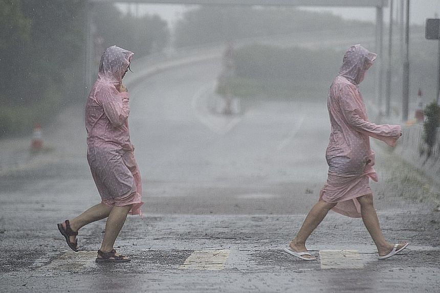 Pedestrians braving the storm yesterday morning when Hong Kong's storm signal was raised to No. 8, the third-highest level.